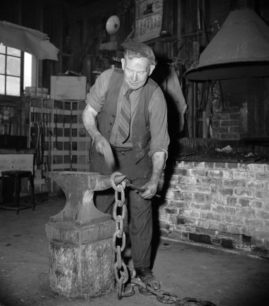 vintage blacksmith forging chain on anvil in workshop