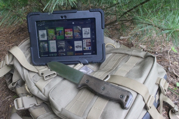 survival kindle library amazon fire next to large knife and daypack