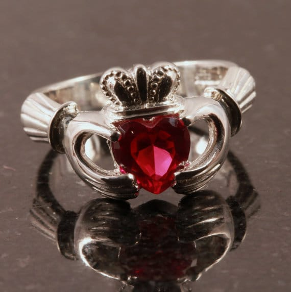 Ruby claddagh engagement ring placed on table.