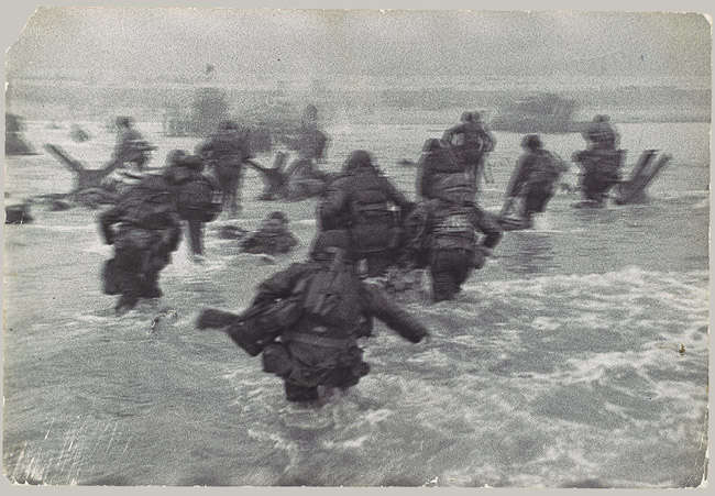 D-day Normandy photo men storming beaches through shallow seawater.