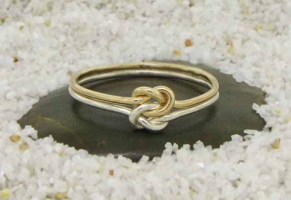 Two color knot engagement ring placed on black stone.