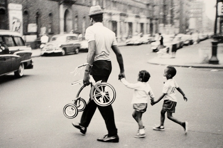 Vintage African American black father walking across street with young children.