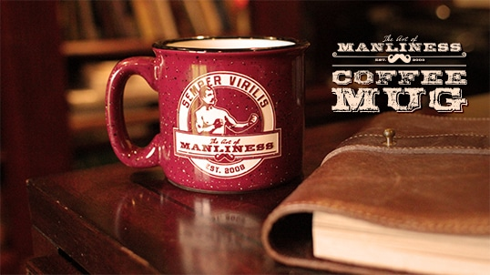 Art of Manliness Coffee Mug and a Book Placed at table.