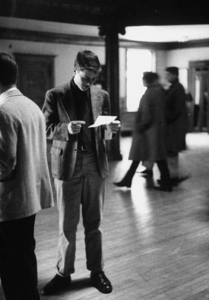 vintage young man reading letter in open lobby