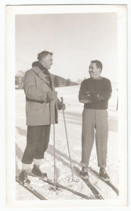 Vintage men on skis talking smiling small talk.
