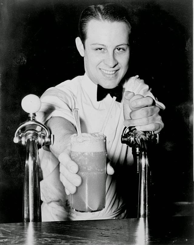 Vintage soda fountain worker pouring new York egg cream.