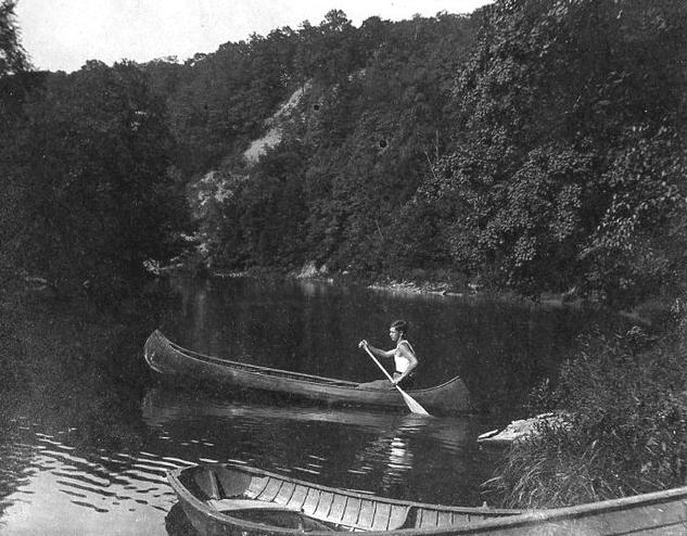 Vintage man rowing boat in wilds.
