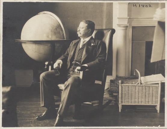 teddy theodore roosevelt sitting portrait next to giant globe