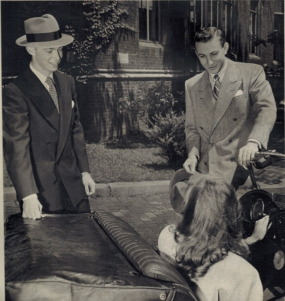 Vintage college men talking with woman in car.