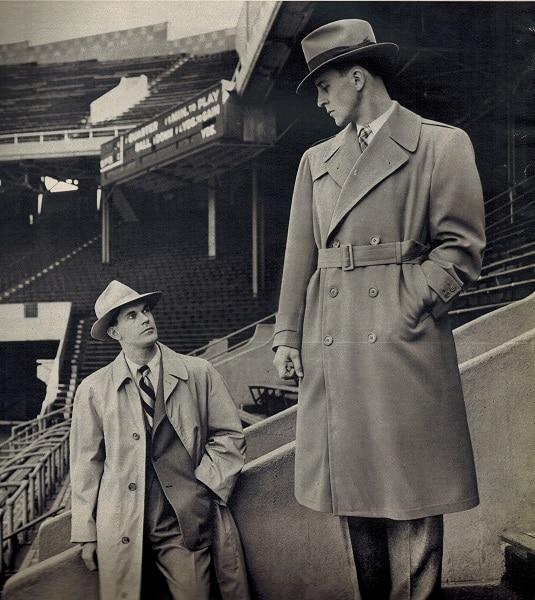 Vintage college men wearing rain coats in stadium.