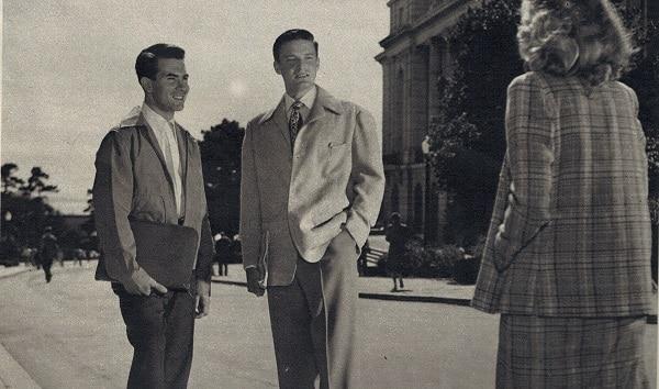 A woman walking toward men standing in suit.