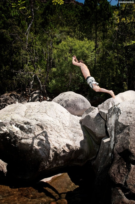 man jumping off large rock into lake