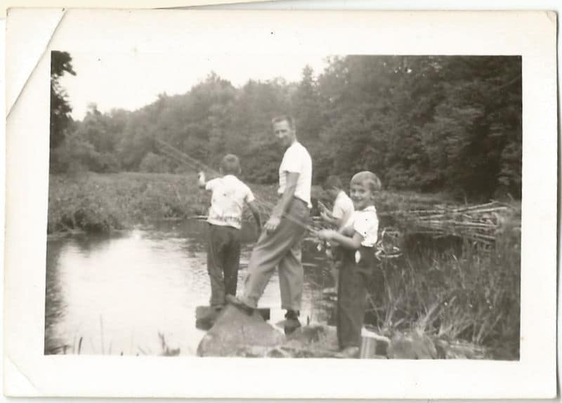 Vintage father and sons fishing in pond.