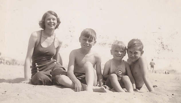 Vintage mother and sons at beach in swimsuits.