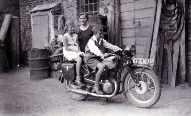 Vintage mom posing with children on motorcycle.