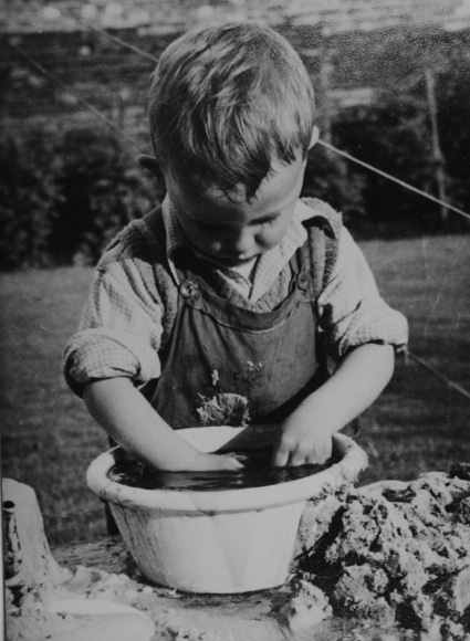 vintage little boy with hands in mud