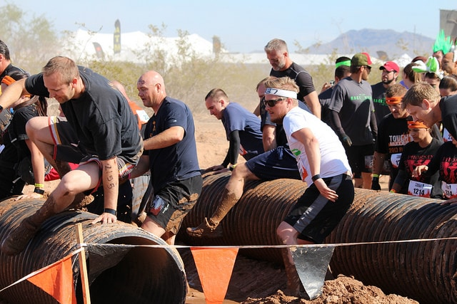 Sport men participating in obstacle race competition over jumping tubes.
