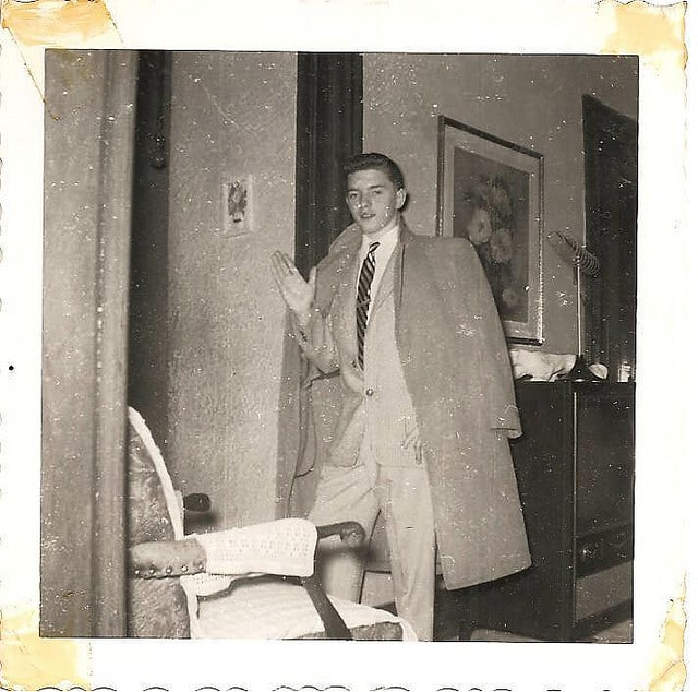 Vintage young man wearing large overcoat and posing.