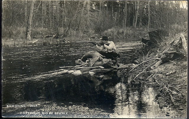 vintage hunter on riverbank aiming rifle