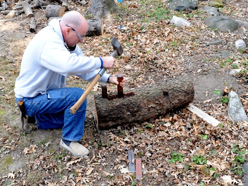 man splitting log in half with wedges and maul