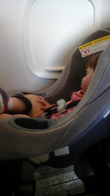 baby sleeping in carseat on airplane next to window