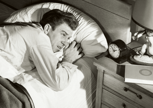 vintage man in bed looking annoyed at clock