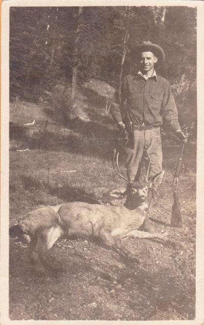 vintage hunter posing with deer kill