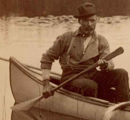 vintage man with stern look in canoe paddling water