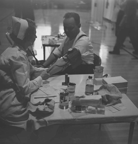 vintage man at nurse's table having blood pressure taken
