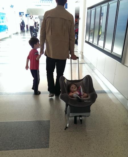 man walking through airport wheeling baby in carseat
