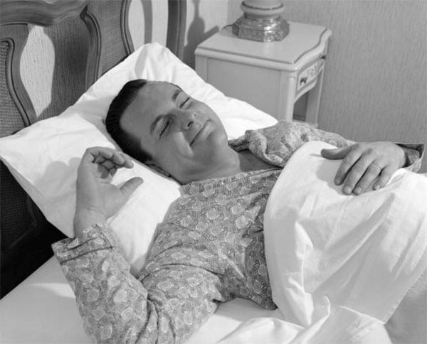 vintage man in bed sleeping with smile happy look on face