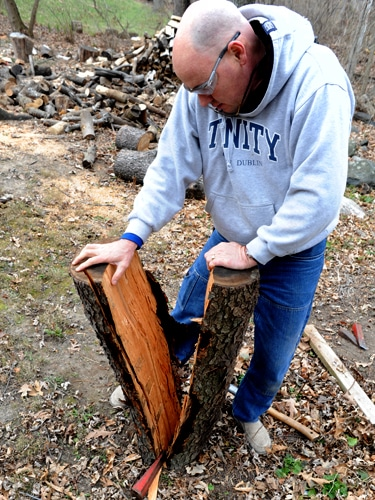 Men Cut the wood with a hatchet and separate into two pieces.
