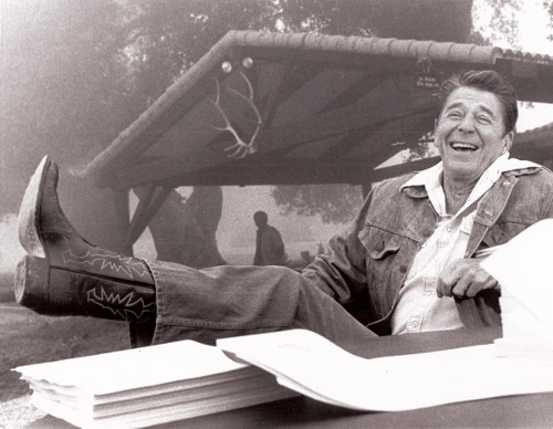 Ronald Reagan wearing cowboy boots feet up on table.