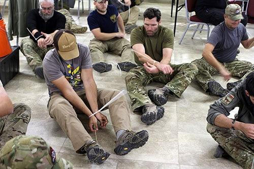 Men using a kevlar string through zip ties.