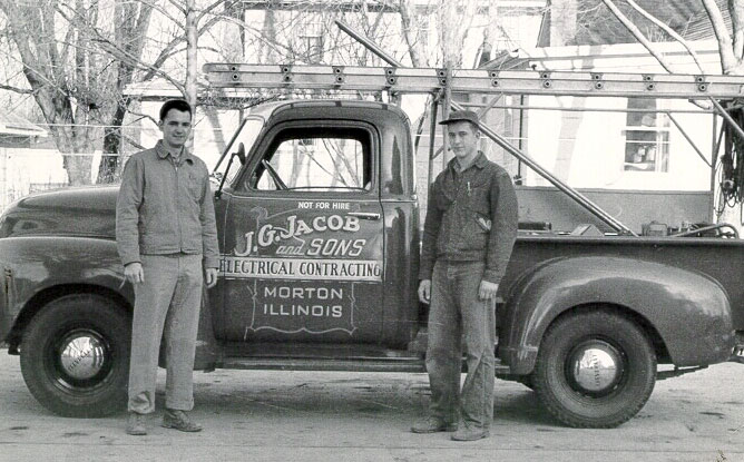 Vintage electricians standing in front of company Truck.