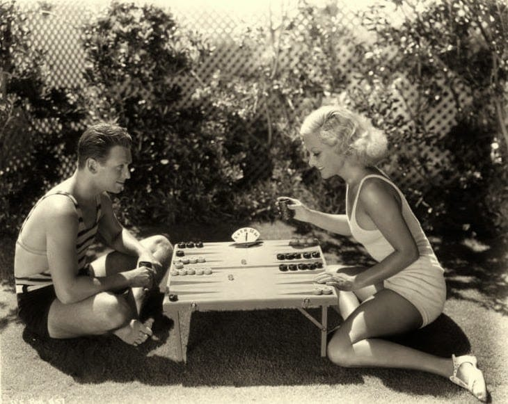 Vintage couple playing backgammon on short Table.