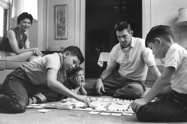vintage family playing board game on living room floor