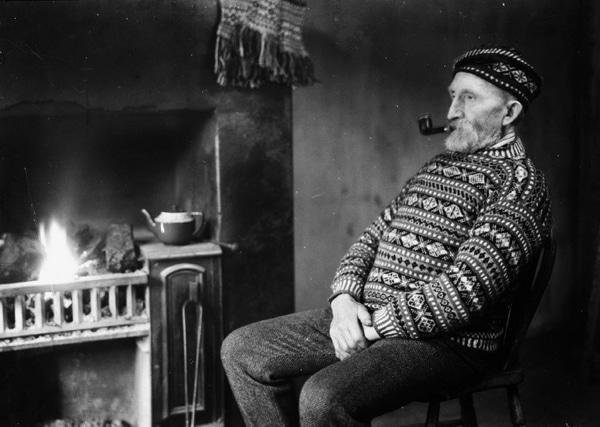 vintage old man in sweater next to fireplace smoking pipe