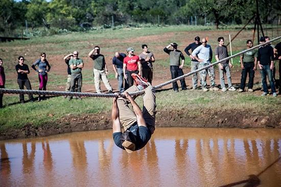 atomic athlete vanguard man hanging from rope over mud pit