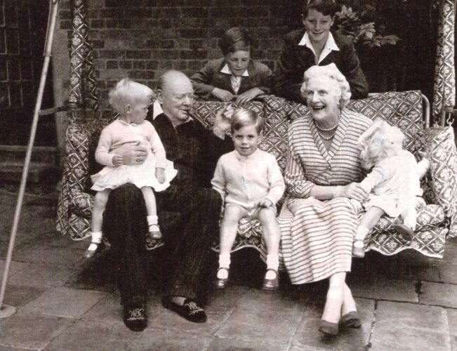 Winston Churchill with wife and grandchildren on outdoor swing.