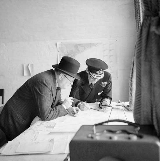 Winston Churchill looking at war map with general.