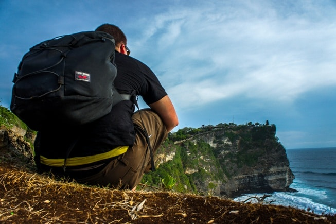 Man sitting on edge of Cliff with Backpack.
