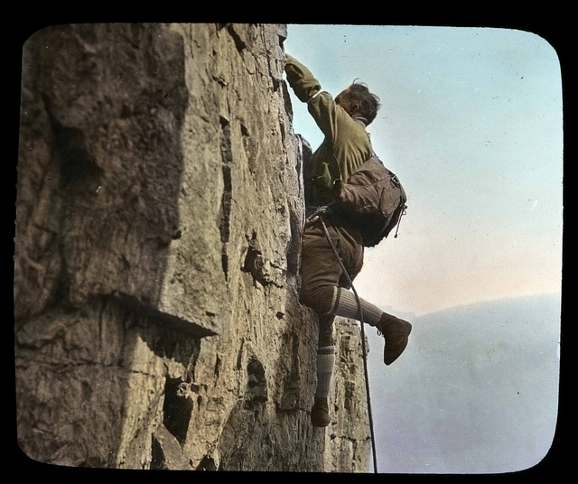 Vintage man scaling climbing rock cliff wall.