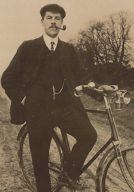 Vintage man on bicycle wearing suit smoking pipe.