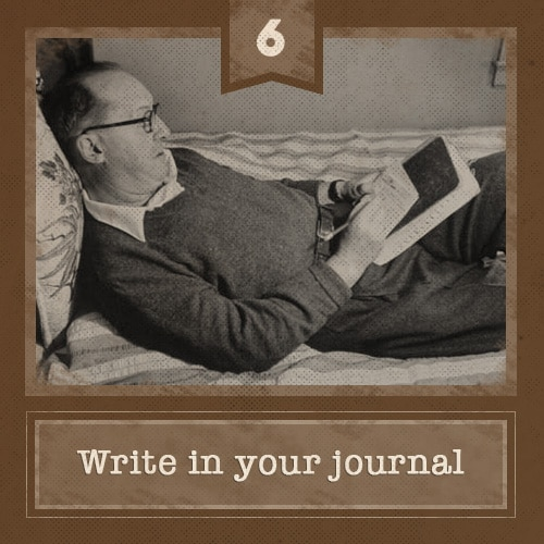 vintage man lying in bed writing in journal