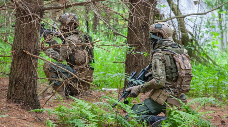 Men in camo camouflage airsoft guns war games.