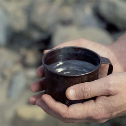 man's hands holding cup of water close up photo
