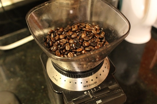grinding coffee beans in burr grinder