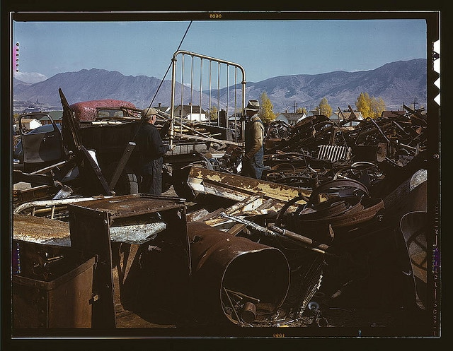 Scrap metal yard 1970s 1980s men in middle of junk.