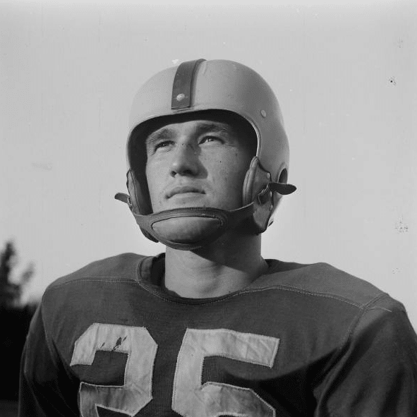 vintage football player in uniform and helmet staring off